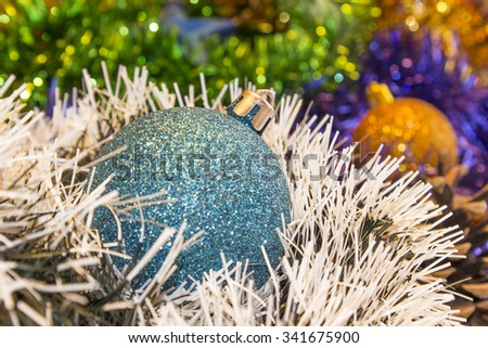 Background for New Year's and Christmas cards. Celebratory  holiday bright rainbow decorations for Christmas trees or pine. Focus on  blue toy - stock photo