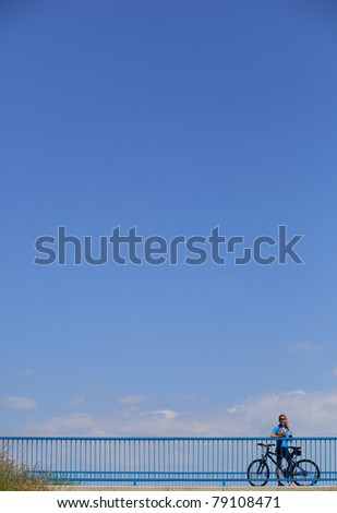 Background for poster or advertisment pertaining to cycling/sport/outdoor activities - female cyclist during a halt on a bridge against blue sky