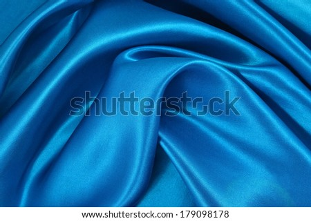 Background from a blue satin fabric with picturesque folds - stock photo