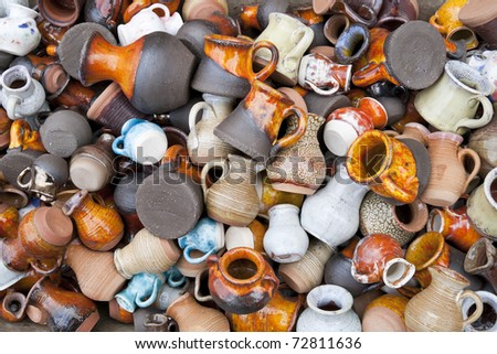 Background from small ceramic multicolored jugs and cups. Mass production, selective focus - stock photo