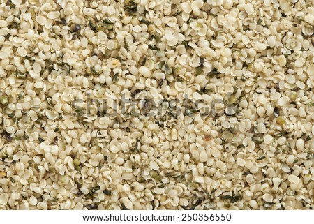 background full of fresh healthy and tasty broken hemp seed - stock photo