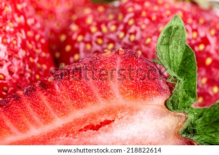 background half of the strawberry on the background of strawberries macro - stock photo