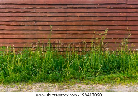Background horizontal blank wooden fence overgrown with tall grass in the countryside near footpath  - stock photo
