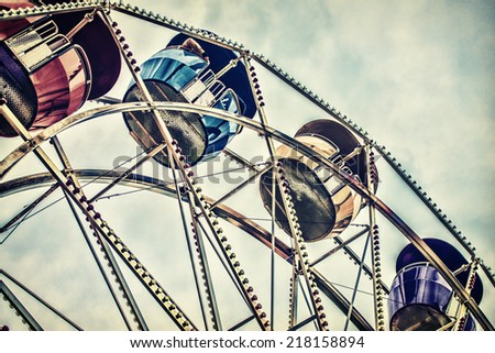 Background image of a close up low angle view of ferris wheel passenger cars high up against a cloudy sky at an amusement park.  Filtered for a retro, vintage look.     - stock photo