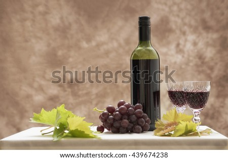 Background image of a red wine bottle with two glasses, red grapes and vine leaves. Taken with copy space. - stock photo