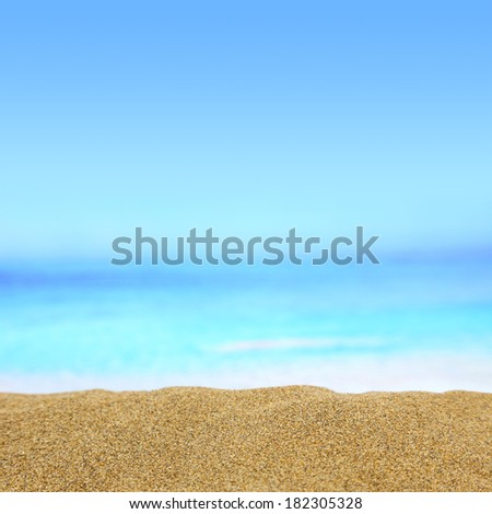 Background image of golden sand with sea on the background - stock photo