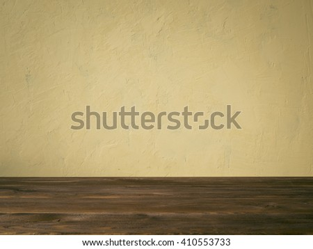 Background image of the biege concrete wall and wooden table