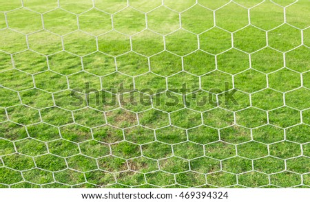 Background image of white soccer net on blur green grass of football field.