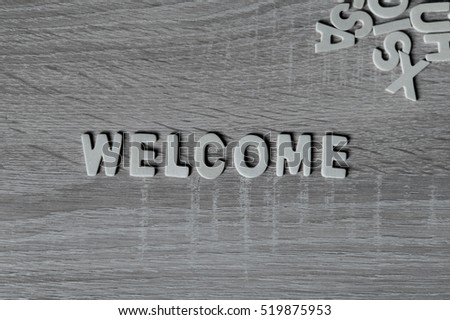 "Background. Letters on wooden table. ""Welcome""."
