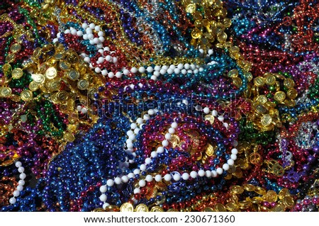 Background made up of mulit-colored including gold, purple, blue, green and pink mardi gras beads