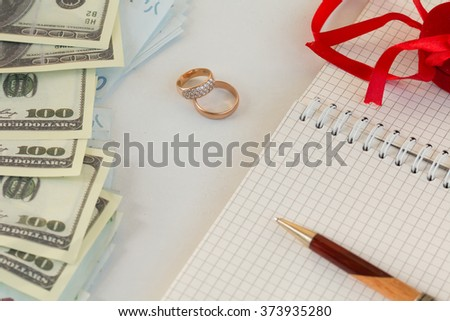 background, money , wedding rings , notebook notes pen, prepare for the wedding