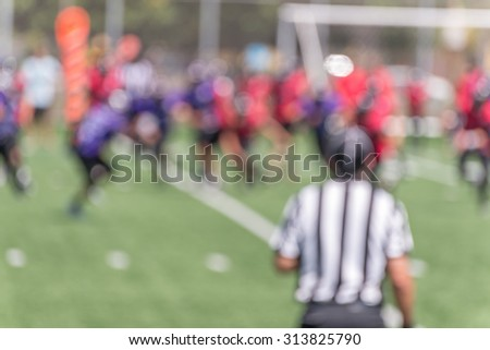 background of a blurred American football game  with football players in the green field with a referee