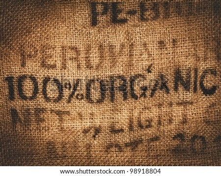 Background of a hessian coffee bag stamped and certified one hundred percent organic - stock photo