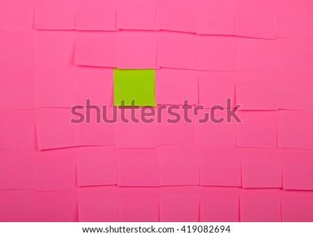 Background of a pink sticky notes. Green sticky note is among pink sticky notes. - stock photo