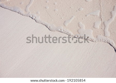 Background of a tropical pink sand with an ocean wave - stock photo