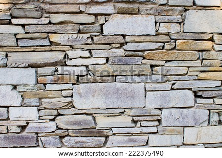 background of a wall with irregular stones - stock photo