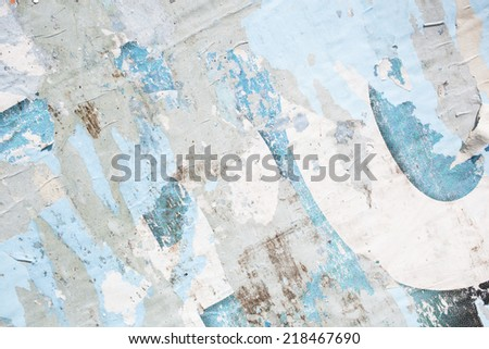 background of an old grungy billboard with rests of riven placards in white, grey blue and black - stock photo