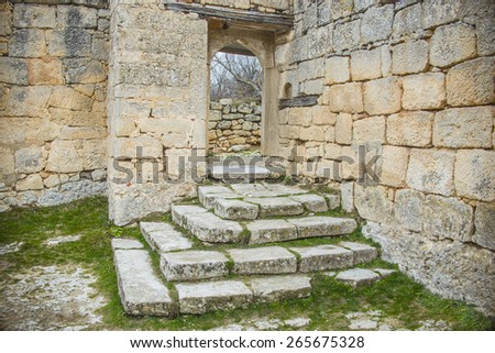 Background of ancient historical old retro vintage aged stone front yellow and gray wall texture with empty Door frame, and Staircase in antique style Fresh spring green grass Empty space No people - stock photo