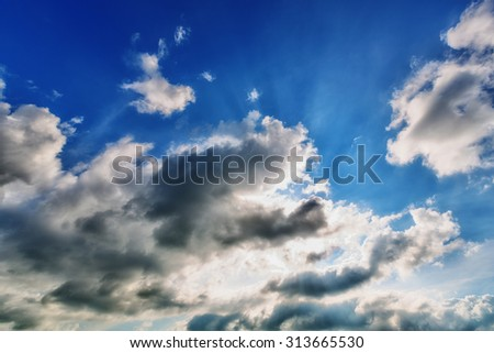 Background of blue cloudy sky with sun rays