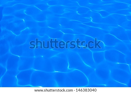 background of blue water in the pool with the reflection of the sun - stock photo