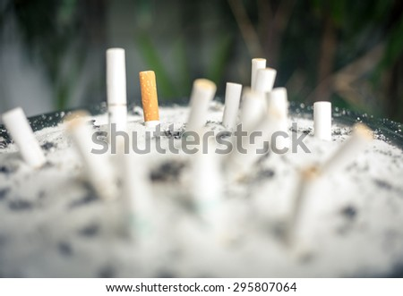 Background of Blurry cigarette butts in the ashtray dirty. Smoking people will get lung cancer and more disease soon. vintage tone. - stock photo