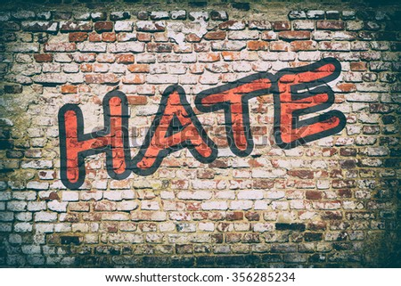 Background of brick wall with word hate graffiti.