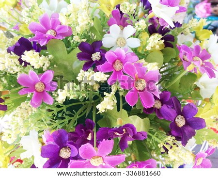 Background of bright colorful artificial flowers. Close up.