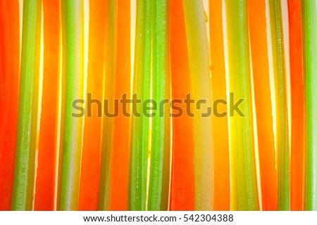 background of bright orange strips of fresh carrots and celery