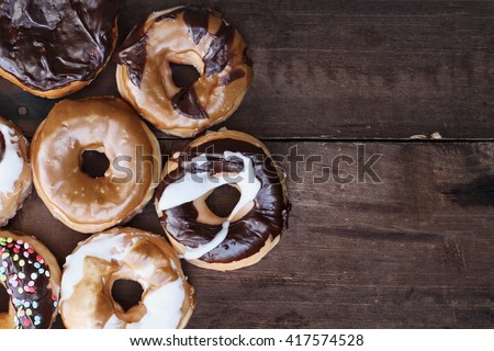 Background of chocolate, carmel, glazed and filled donuts over a rustic background with copy space. Image shot from overhead. - stock photo