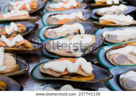 background of clams in shells lying in a row with spices - stock photo