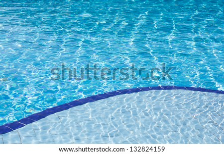 Background of clear blue water with sun reflections in an outdoor swimming pool with two different depths, a shallow and a deep depth.