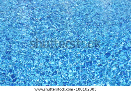 Background of clear water in an outdoor swimming pool with blue tiles.