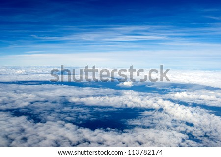 background of clouds. view from the airplane. Top view. continuous carpet of clouds against a blue sky - stock photo