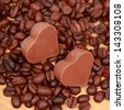 Background of coffee beans/Delicious chocolate heart symbol candies and dark brown coffee beans - stock photo