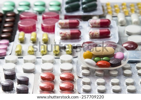background of colored pills, tablets and capsules in blisters - stock photo