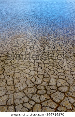 Background of cracked dry land covered with a thin layer of water - stock photo