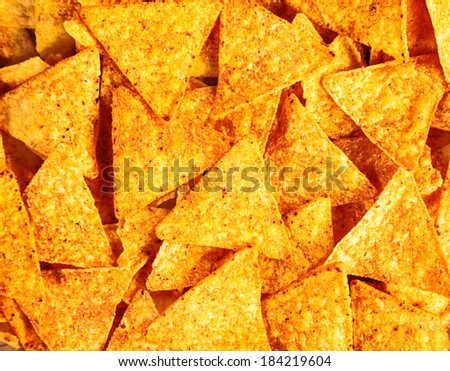 Background of crisp crunchy spicy corn tortillas or nachos with their ditsinctive triangular shape for a tasty snack - stock photo