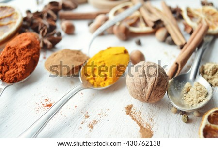 Background of different spices.  Various Fresh Herbs and Spices, Onion Slices, and Hot Peppers Scattered on Dark Gray Stone Surface with Copy Space