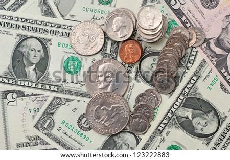 Background of dollar banknotes and coins, with selective focus.