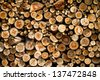 Background of dry chopped firewood logs stacked up in a pile - stock