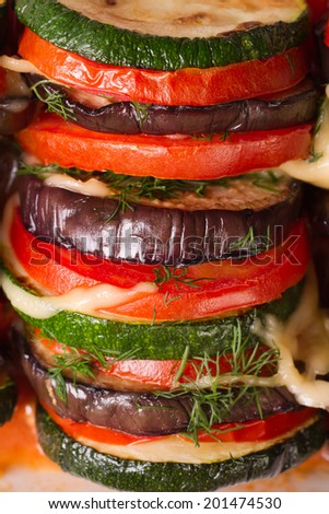 background of eggplant, zucchini and tomatoes baked with cheese and herbs macro vertical