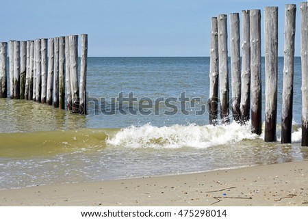 background of empty beach at the coastline of the sea with a row of poles in the surf water