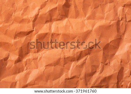 Background of empty wrinkled orange paper. Backdrop texture with copyspace and rough rumple surface.