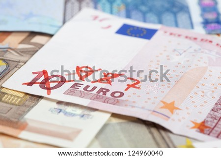 Background of Euro banknotes on the ground, one 10 Euro note with 9, 8, 7... written on it as a symbol of devaluation.  Short Depth of field with front and back part blurred out of focus. - stock photo