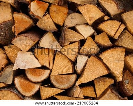 Background of firewood stacked in the woodpile. - stock photo