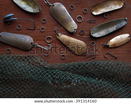Background of fishing stuff. Lures and Hooks with grid for fish on a wooden table . - stock photo
