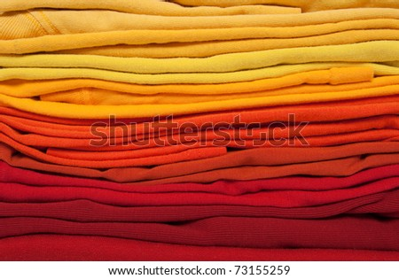 Background of folded red, orange and yellow clothes. Warm colors. - stock photo