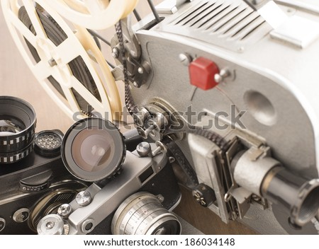 Background of Four objects Vintage old movie and photo camera with lens a reel of film Projector - stock photo