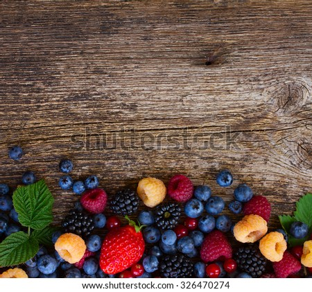 background of fresh  berries mix on wooden tabletop with copy space - stock photo
