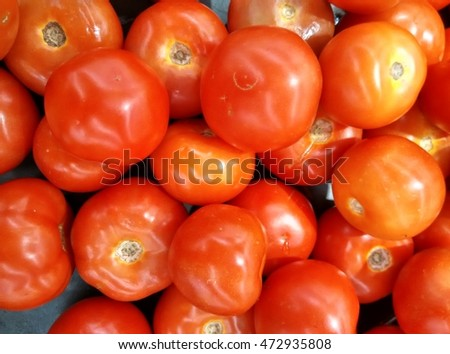 background of fresh organic ripe sweet red tomato on display for sale at local farmer's market departmental store